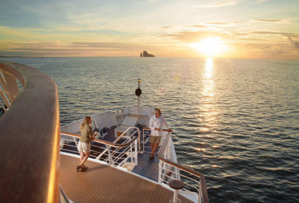 Guests on the sun deck of the expedition vessel observing the sunset in the Galapagos Islands.