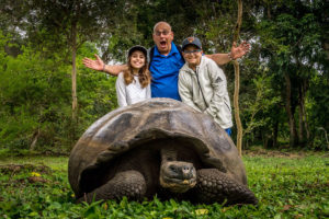 Family poses behand a giant tortoise in Galapagos