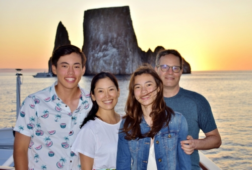 Family posing with the iconic Kicker Rock in the Galapagos Islands